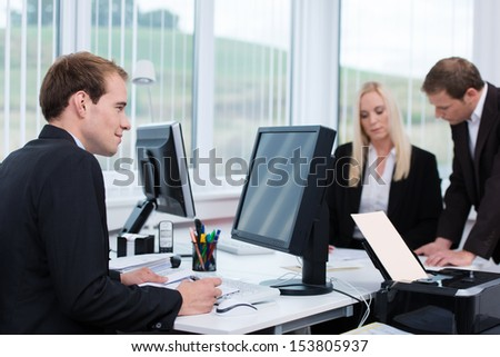 Dedicated businessman working at his desk in the office taking notes from information on the computer monitor - stock photo
