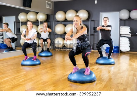 Dedicated group trains squats on half ball at fitness gym - stock photo