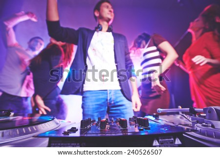 Deejay equipment and dancing group of friends - stock photo