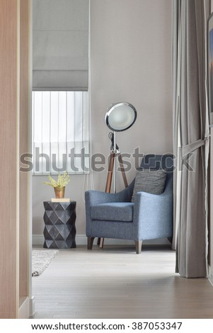 Deep blue armchair with stylish standing lamp in the corner of living room - stock photo