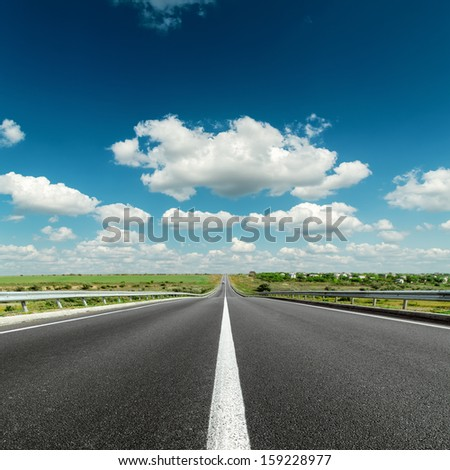 deep blue cloudy sky over asphalt road - stock photo