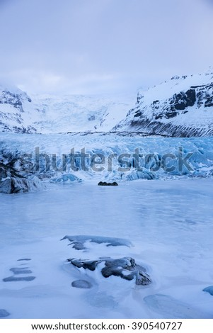 Deep blue colour of Svinafell Glacier in Skaftafell National Park with tent on frozen lagoon, Iceland - stock photo