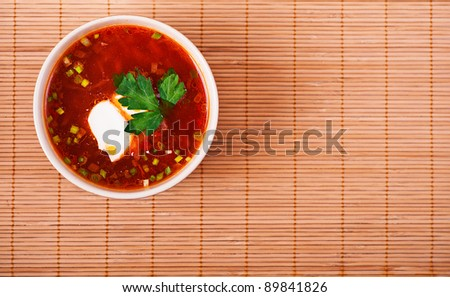 deep dish of beet soup and cabbage seasoned with sour cream and decorated with sprig of parsley on background of bamboo towels - stock photo