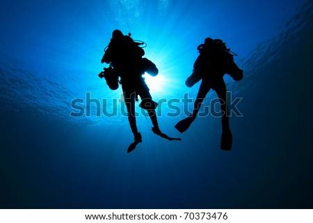 Deep Explorer Technical Divers silhouetted against sunburst - stock photo