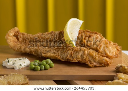 Deep fried dory fish with sliced lime on top served on wood platter - stock photo