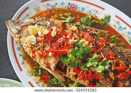 Deep fried fish topped with sweet and sour sauce. Thai food. Selective focus. - stock photo