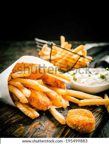 Deep fried takeaway crumbed fish portions and golden potato chips served in a disposable paper cone with tartar sauce on an old wooden table in a restaurant or fish shop - stock photo