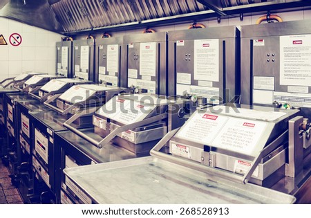 Deep fryers on restaurant kitchen, all trademarks removed, toned image - stock photo