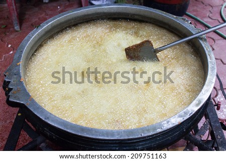 Deep frying in oil. Chicken in boiling oil. Cooking. Coconut Oil in huge tumbler.oil pattern.golden shining yellow oil boiling and creating bubbles. oil bubbles texture - stock photo
