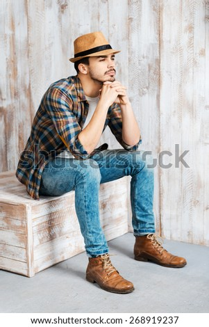 Deep in his thoughts. Handsome young man wearing hat and looking away while sitting against the wooden wall  - stock photo