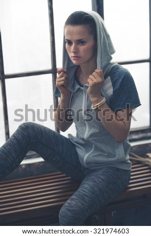 Deep in thought, a woman pauses, sitting on a loft gym bench, while holding her hoodie up on her head, as she thinks about the workout she has just done. - stock photo