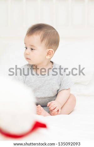 Deep thinking cute baby boy sitting with Teddy bear in the bedroom - stock photo