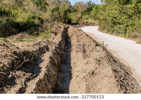 Deep water canal in the woods made by tractor excavator - stock photo