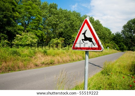 Deer crossing sign and road - stock photo