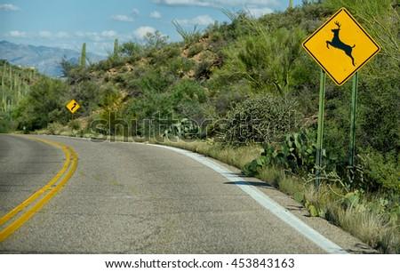 deer crossing warning sign on curvy street in arizona - stock photo