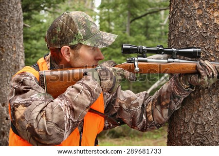 deer hunter aiming rifle in woods - stock photo