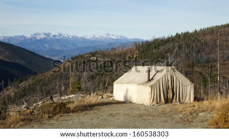 Deer Hunting Camp in the Mountains with an old canvas wall tent and a wood stove chimney pipe. National Forest wilderness camping in fall / autumn Washington Oregon Montana Idaho Wyoming Colorado - stock photo