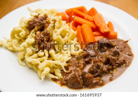 Deer stew with Spaetzle and carrots - stock photo
