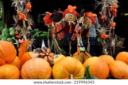 Deerfield, Massachusetts - September 20, 2014:   A seasonal display of pumpkins, Indian corn, and scarecrow decorations at a roadside farm stand - stock photo