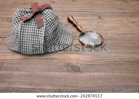 Deerstalker or Sherlock Hat and magnifying glass on Old Wooden table - stock photo
