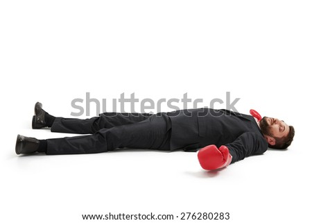 defeated businessman in formal wear and red boxing gloves lying on the floor over light grey background - stock photo