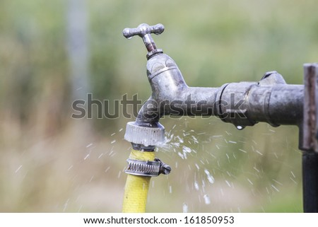 Defective faucet. Water tap spilling water - stock photo