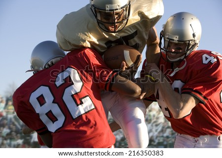 Defenders tackling running back carrying football - stock photo