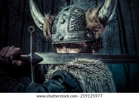 Defense, Viking warrior, male dressed in Barbarian style with sword, bearded - stock photo
