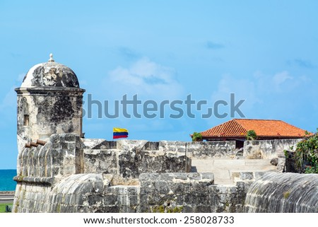 Defensive wall surrounding the historic center of Colombia with a Colombian flag waving in the breeze - stock photo