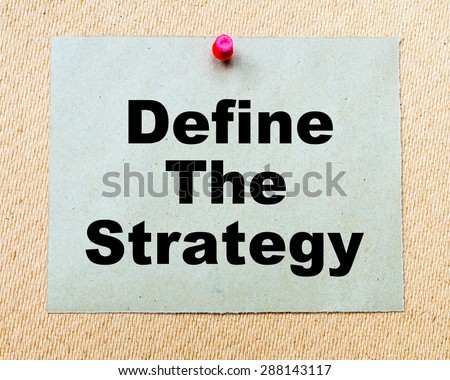 Define The Strategy  written on paper note pinned with red thumbtack on wooden board. Business conceptual Image - stock photo