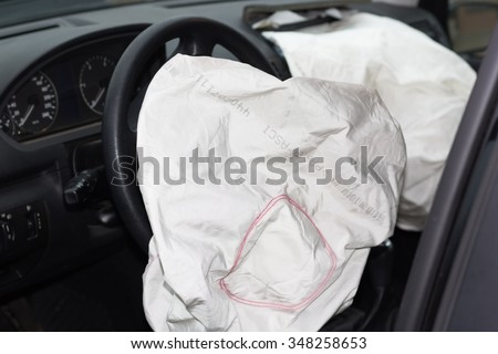 deflated airbags after the erupted inflation due to a car collision - stock photo