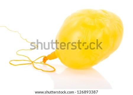 Deflated yellow balloon at a rope; isolated over white - stock photo
