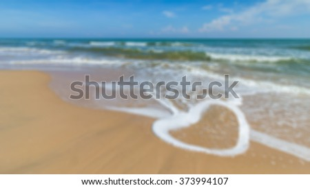 Defocus of heart shape of wave on the beach with blue sky background - stock photo