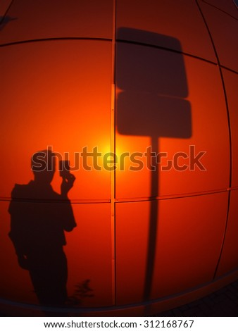 Defocused and blur image of the silhouette on a red-orange wall, who photographs a road sign in the evening at sunset with wide angle fisheye lens and distortion view - stock photo