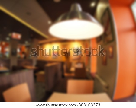 Defocused and blur interior of the restaurant with a bright lamp in the foreground. The image was blurred for use as a background. - stock photo
