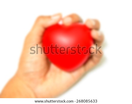 Defocused and blurred image for background of Red heart in hand  - stock photo