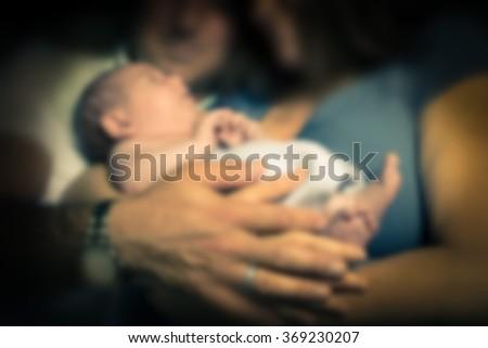 Defocused blur of parents holding newborn baby - stock photo