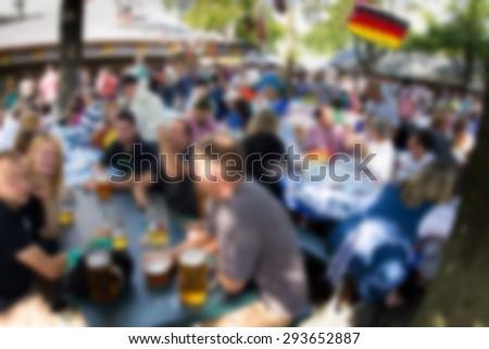 Defocused blur of people in crowded German beer garden - stock photo