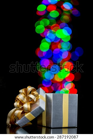 Defocused lights heart shaped are moving out of open gift box - stock photo
