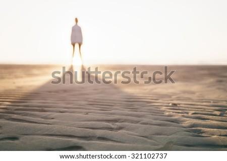 defocused photo of girl standing on beach, long shadow - stock photo