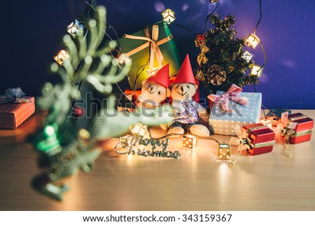Defocused Reindeer. Focus couple bear and ornament, Merry Christmas night light. Christmas tree and other decoration with Lovely bear, a gift,  and ribbon . - stock photo