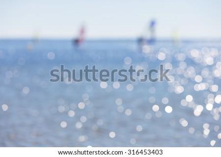Defocused seascape with windsurfers on sea surface. Blurry landscape useful as background - stock photo