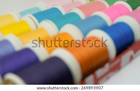 Defocused sewing threads multicolored, blurred background for your design - stock photo
