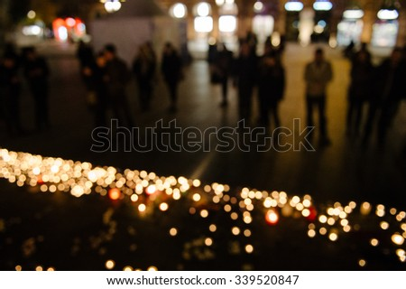 Defocused view of people attend a vigil and light candles in the center of Strasbourg for the victims of the November 13 attacks in Paris that killed at least 128 people - stock photo