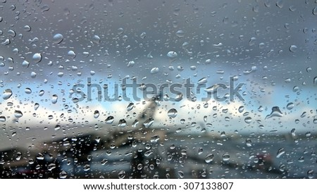 Defocused view on airplane wing through passenger window with rain drops - stock photo