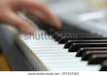 Defocusing hands on the keyboard of the piano - stock photo