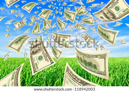 Deformed dollars in the sky and grass. - stock photo