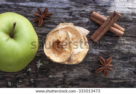 Dehydrated dry apples, between star anise, green malus domestica and cinnamon sticks, on wooden background - stock photo