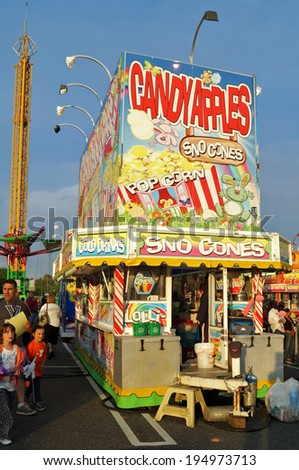 DELAWARE COUNTY, PENNSYLVANIA - May 17, 2014:  People wait in line near a food stall featuring candy apples, popcorn, sno cones and other snacks at a traveling summer carnival. 					 - stock photo