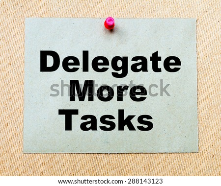 Delegate More Tasks written on paper note pinned with red thumbtack on wooden board. Business conceptual Image - stock photo